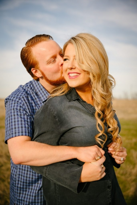 Outdoor engagement photos in open field groom kissing bride on the cheek - Photos by Stephen Karlisch