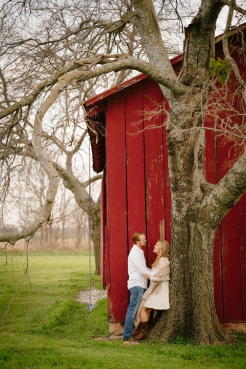 Outdoor engagement photos with couple leaning on tree in front of red barn - Photos by Stephen Karlisch