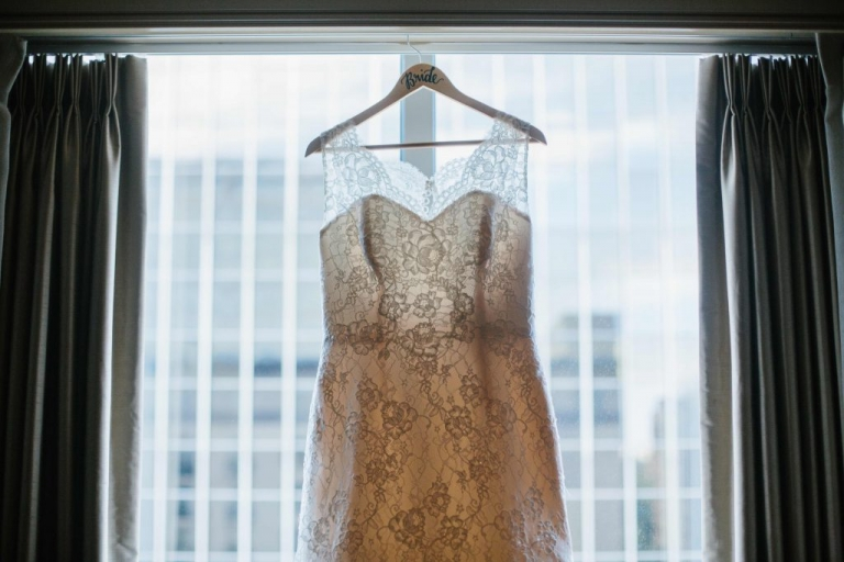 Sleeveless lace wedding dress hanging on personalized wooden hanger with bride written on hanger in window of Dallas hotel room for fall wedding - Photos by Apryl Ann Photography