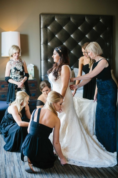 Bride getting dressed with mother and bridesmaids helping zip up dress for fall wedding in Dallas, Texas - Photos by Apryl Ann Photography