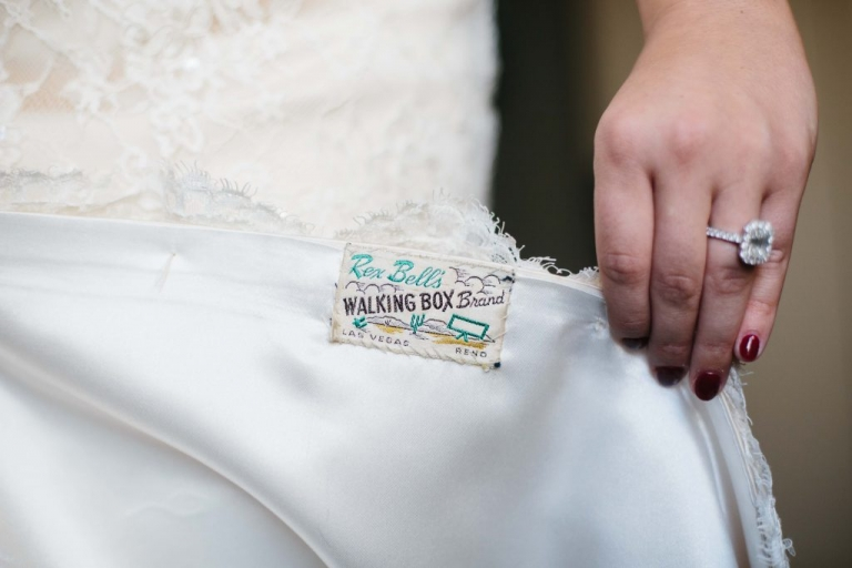 Bride in ivory lace wedding dress for fall wedding in Dallas, Texas with personalized Rex Bells Walking Box Brand Las Vegas Reno patch on inside of dress brides something old - Photos by Apryl Ann Photography