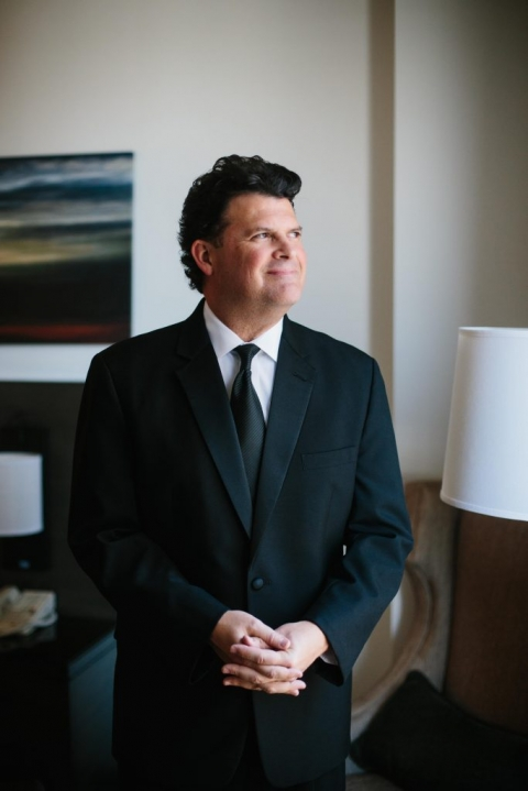 Groom wearing black tuxedo with black tie getting ready in hotel room in Dallas, Texas for fall wedding - Photos by Apryl Ann Photography