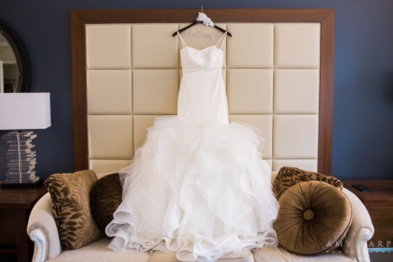 Brides white thin strap wedding dress with full bottom hanging up on personalized brown hanger with brides name for October fall wedding in Dallas, Texas - Photos by Amy Karp Photography