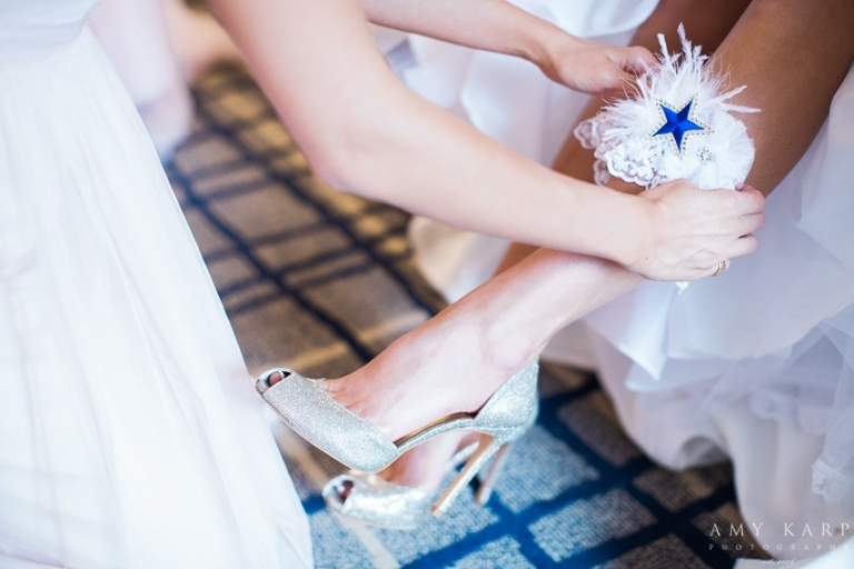 Bride putting on customized Dallas Cowboy Cheerleaders garter before October fall wedding in Dallas, Texas - Photos by Amy Karp Photography