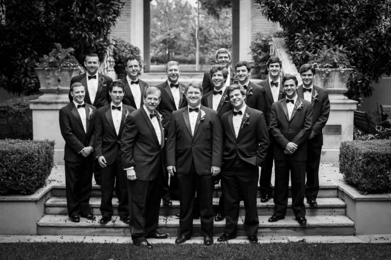 Groom and groomsmen in tuxedos with bowties and boutonnieres before fall wedding at Highland Park United Methodist Church in Dallas, Texas - Photos by Gary Donihoo