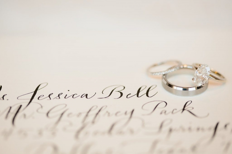 Bride and groom wedding bands and oval shaped engagement ring on classic calligraphy invitation - Photos by The Tarnos