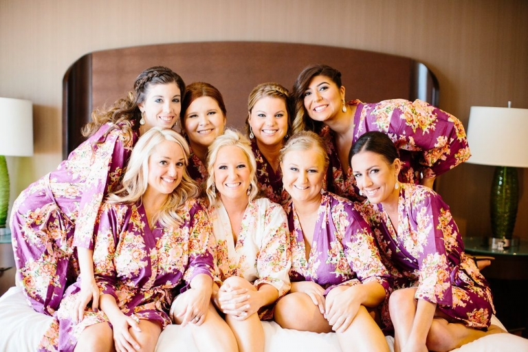 Bride and bridesmaids getting ready for fall wedding in matching purple and white floral robes - Photos by The Tarnos