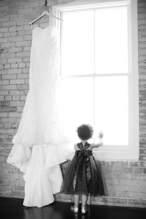 Black and white photos of strapless wedding dress hanging on personalized wedding hanger in window with flower girl standing next to dress looking out window - Photos by The Tarnos