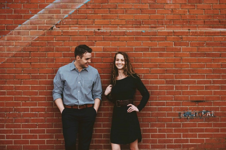 Engaged couple standing in front of red brick wall for outdoor engagement photos - Photos by Stephanie Rogers Photography