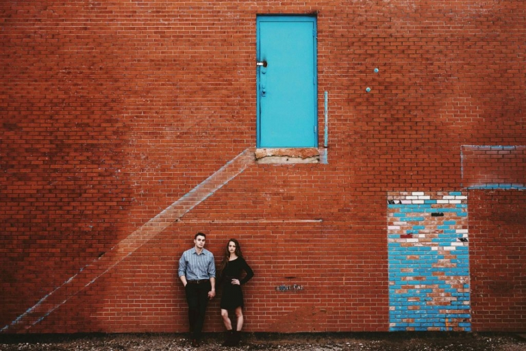 Outdoor engagement photos couple standing in front of red brick wall with turquoise door - Photos by Stephanie Rogers Photography