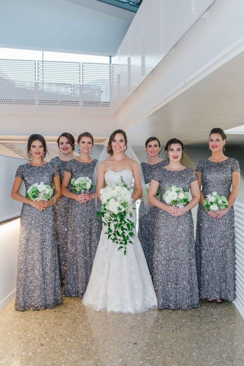 Bride with bridesmaids in long cap sleeved silver sequin dresses with white and green wedding bouquets before fall wedding at Perot Museum in Dallas, Texas - Photos by Katherine O'Brien Photography