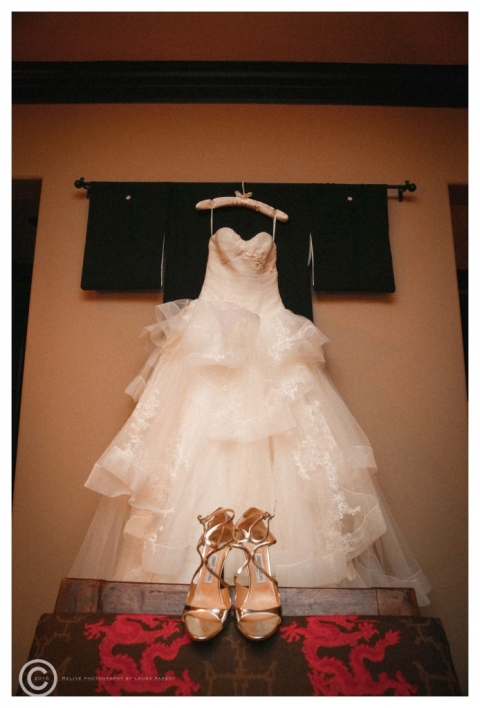 Brides dress hanging in suite with gold Jimmy Choo strappy heels at Hotel Zaza in Dallas, Texas before November winter wedding - Photos by Relive Photography by Laura Parent