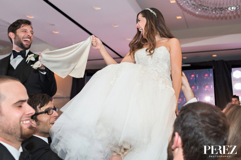 Bride and groom during hora at winter Jewish wedding reception at The Joule Hotel in Dallas, Texas - Photos by Perez Photography