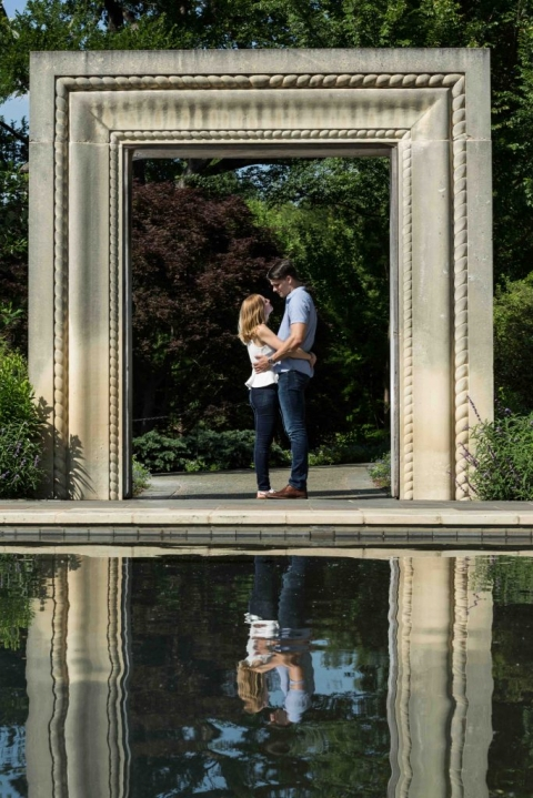 Outdoor engagement photos under stone arch at Dallas Arboretum in Dallas, Texas - Photos by RAP Photography
