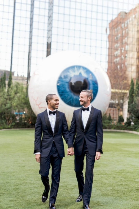 Outdoor winter engagement photos in front of giant eyeball art installation in Downtown Dallas, Texas with two grooms for Winter Wonderland formal wedding - Photos by Shannon Skloss Photography