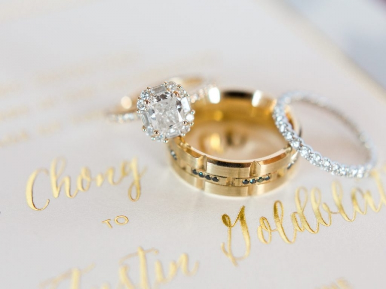Brides all diamond wedding band and grooms gold wedding ring with emerald stones for summer jewish wedding at Hickory Street Annex in Dallas, TX - Photos by Elisabeth Carol Photography