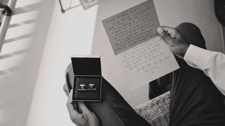 Groom reading note from bride while opening pre wedding vow renewal gift - Photos by Jenny & Eddie