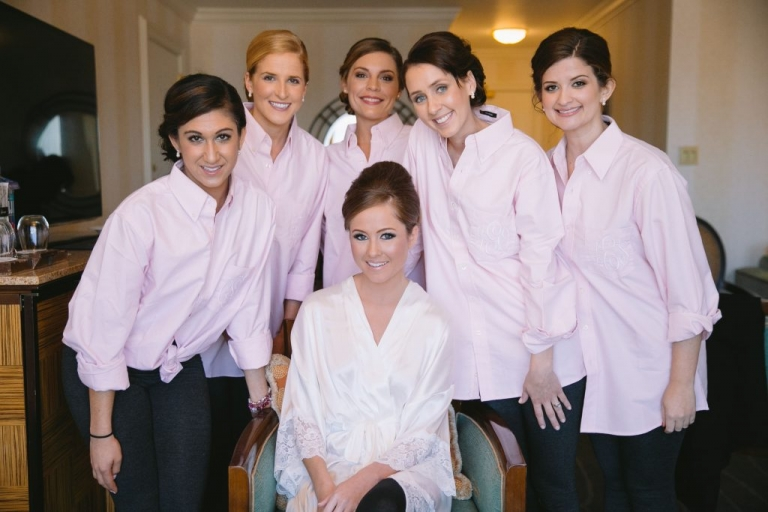 Bride and bridesmaids after getting hair and makeup done bridesmaids in matching pink monogrammed button up shirts bridesmaid gifts - Photo by Evan Godwin Photography