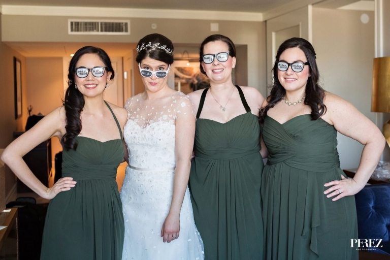 Bride and bridesmaids wearing funny glasses before spring wedding ceremony in Dallas, Texas bridesmaids in dark green strapless floor length dresses - Photos by Perez Photography