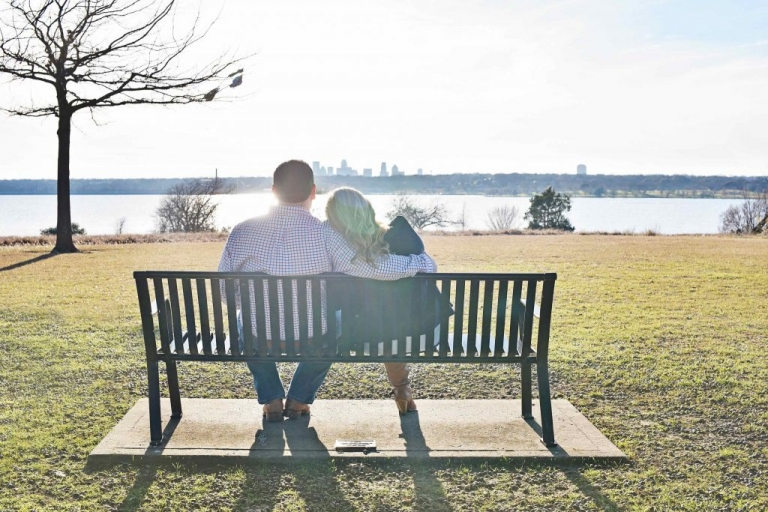 Outdoor engagement photos in Dallas couple sitting on bench overlooking lake - Photos by Adrian Faubel photography