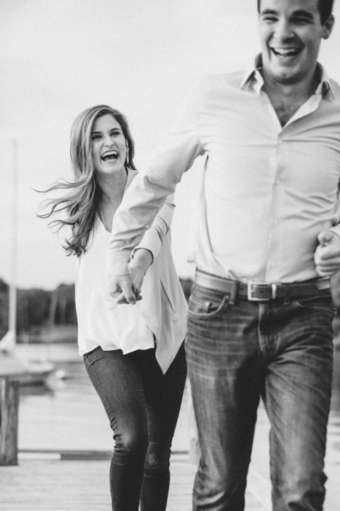 Couple holding hands and laughing during outdoor engagement photos in Dallas, Texas - Photos by Rae Portraits