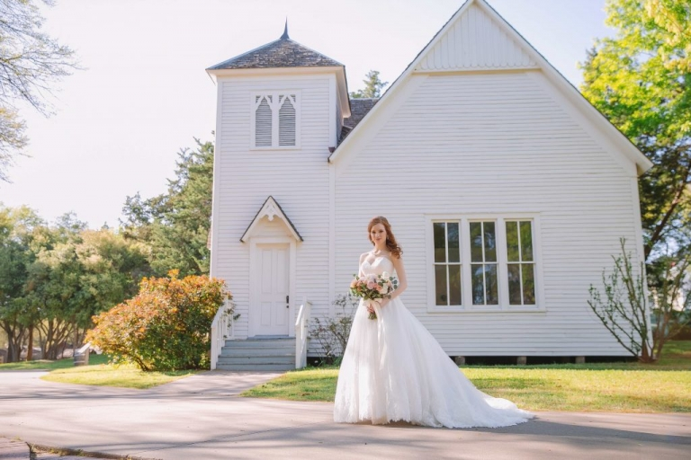 Bride posing in front of chapel at Dallas Heritage Village before spring wedding - Photo by Evan Godwin Photography
