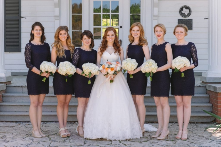 Spring wedding at Dallas Heritage Village with bridesmaids in short navy lace dresses in different styles with white hydrangea bouquets - Photo by Evan Godwin Photography