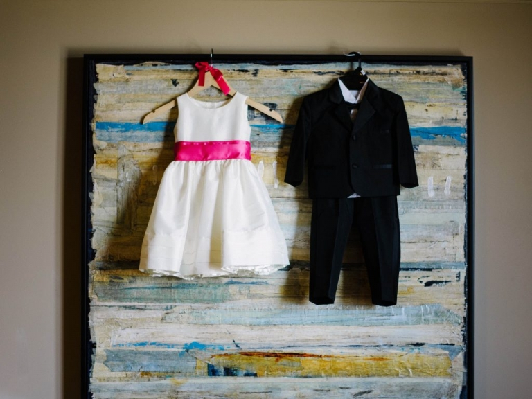 Flower girl and ring bearer outfits hanging up before summer wedding ceremony in Dallas, TX - Photos by The Waldron Photography Company