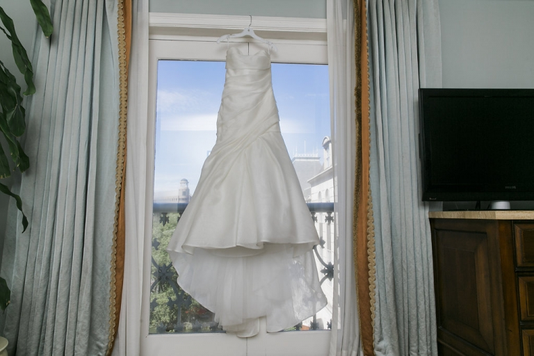Brides strapless wedding dress hanging in window at Hotel Crescent Court before fall wedding in Dallas, Texas - Photos by Havi Frost Photography