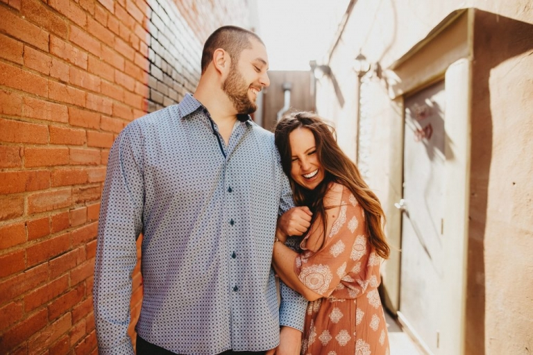 Outdoor engagement photos near red brick wall - Photo by Two Pair Photography