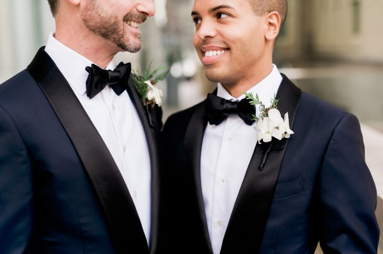 Two grooms in navy and black custom made Tom Ford tuxedos for winter wedding at The Joule Hotel in Dallas, Texas - Photo by Shannon Skloss Photography